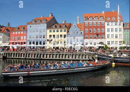 Canal tour boat turning around in crowded Nyhavn on a warm and sunny summer day full of tourists and visitors also - Stock Photo