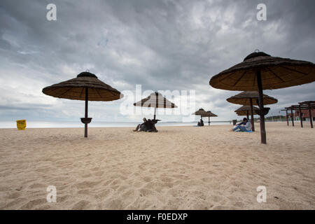 Unidentified people sitting under wood made umbrellas on the beach of Sopot in Poland. It is raining and the sky - Stock Photo