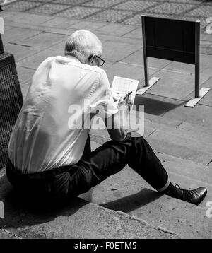 Photo of an elderly man sitting on steps and doing a crossword or sudoku puzzle - Stock Photo