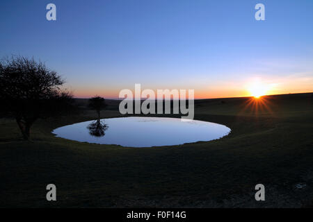 The sun setting behind a dew pond on the South Downs, near Ditchling Beacon, East Sussex. - Stock Photo