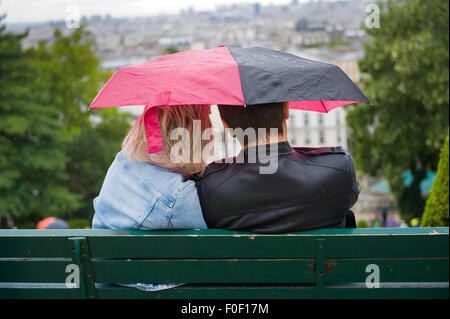 PARIS, FRANCE - JULY 27, 2015: A couple is sitting on a bench under an umbrella during a rainy day in Mont Matre - Stock Photo