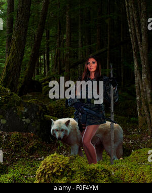 An American Indian woman in camouflage stops, with her gray wolf companion in a forest/ - Stock Photo