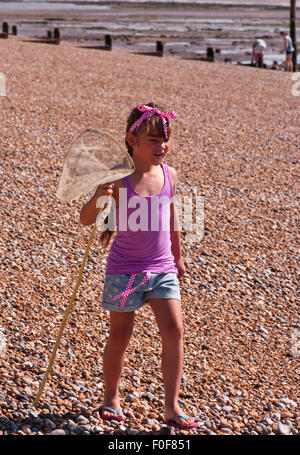 7 year old Girl Walking Over A Shingle Beach With A Fishing Net Dressed in Summer Clothing - Stock Photo