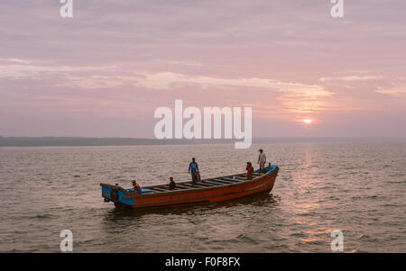 A team of fishermen set out in a small wooden boat for a day's deep sea fishing off the Malabar Coast. - Stock Photo