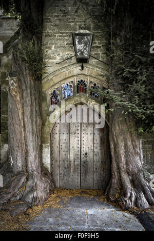 The north door of St Edwards church with two ancient yew trees either side, Stow on the Wold, Gloucestershire, England, - Stock Photo