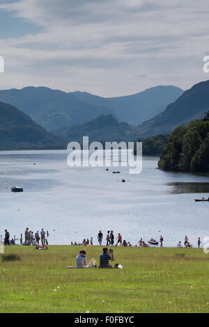 people relaxing in the park looking towards Derwentwater near Keswick in the Lake District, Cumbria, UK - Stock Photo