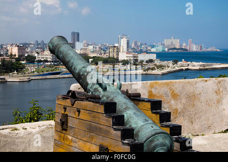 Old cannon at Fortaleza de San Carlos de la Cabana in Cuba pointing over Havana bay towards Havana skyline. - Stock Photo