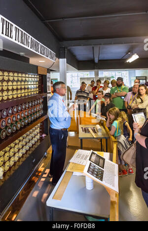Visitors listening to a talk about the rebuilt Turing Bombe codebreaking machine, Bletchley Park, Buckinghamshire, - Stock Photo