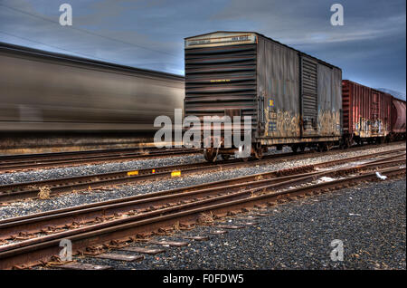 A fast moving freight train is blurred behind a static box car on the fore ground train track - Stock Photo