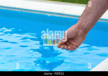 Tester for pool in a hand against the background of the swimming pool. - Stock Photo