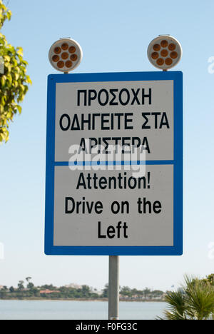 Road sign 'Attention! Drive on the left!' with the Salt lake as a background closeup. Larnaca. Cyprus. - Stock Photo