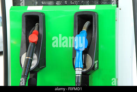 Clouse up of green pump nozzles in gas station - Stock Photo