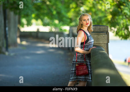 Portrait of young beautiful woman standing in the city Park. - Stock Photo