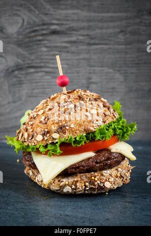 Gourmet hamburger with swiss cheese and fresh vegetables on multigrain bun over dark background - Stock Photo