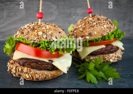 Two gourmet hamburgers with swiss cheese and fresh vegetables on multigrain buns over dark background - Stock Photo