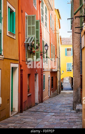 Row of colourful old buildings with bright window shutters along cobblestone street in medieval town Villefranche - Stock Photo