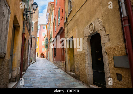 Narrow cobblestone street in medieval town Villefranche-sur-Mer on French Riviera, France. - Stock Photo