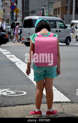 Children japanese girl waiting cross over road at crosswalk traffic road near Gojo subway station on July 11, 2015 - Stock Photo