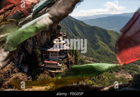 Taktsang or Tiger's Nest Monastery with colourful prayer flags in the foreground Paro Valley Bhutan - Stock Photo