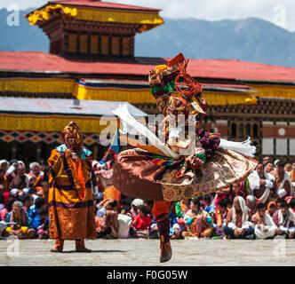 Dance of terrifying deities (Tungam) with spectators in the background Paro religious festival Bhutan - Stock Photo