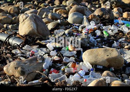 Empty plastic bottles on rocky coast - Stock Photo