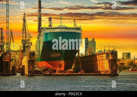Ship being repaired in dry dock at sunset in Gdansk, Poland. - Stock Photo