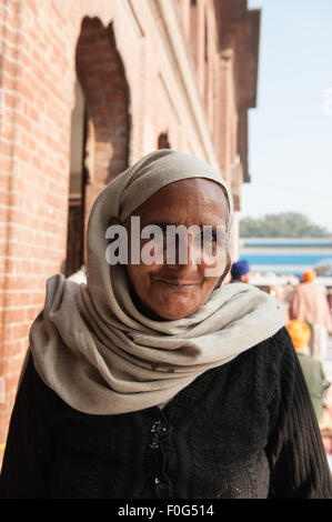 Amritsar, Punjab, India. A smiling woman worshipper with headscarf at the Sri Harmandir Sahib Golden Temple. - Stock Photo