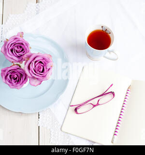 three pink roses in vases on blue plate with mug of tea and open notebook with glasses and pencil - Stock Photo