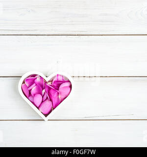 a white heart shaped bowl filled with pink rose petals, on a whitewashed wooden background - Stock Photo