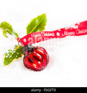 round red bauble with holly and Merry Christmas ribbon on snow - Stock Photo