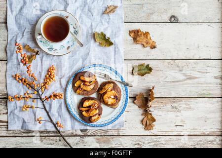 pancakes with caramelised apples on vintage plate, with tea in vintage teacup, oak leaves and ilex berries - Stock Photo