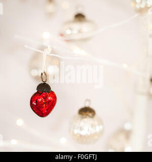 closeup of a heart-shaped red glass bauble with silver baubles and bokeh in the background - Stock Photo