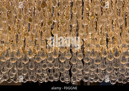 Backlit teardrop shaped glass beads of a chandelier glow at a lamp shop in the Grand Bazaar, Istanbul, Turkey. - Stock Photo