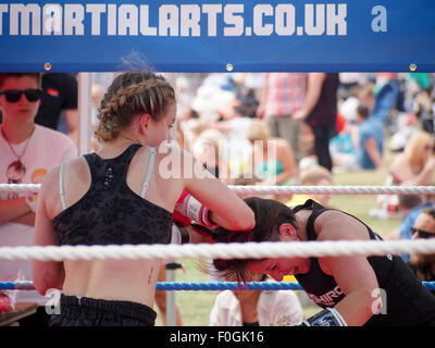 Female Muay Thai boxers, fighting in an outdoor ring - Stock Photo