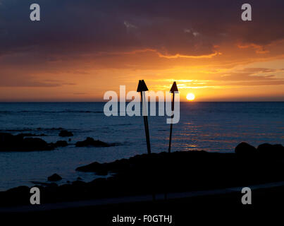 A view of a gorgeous tiki torch sunset as viewed from the Brown's Beach House at the Fairmont Orchid, Kohala Coast, - Stock Photo