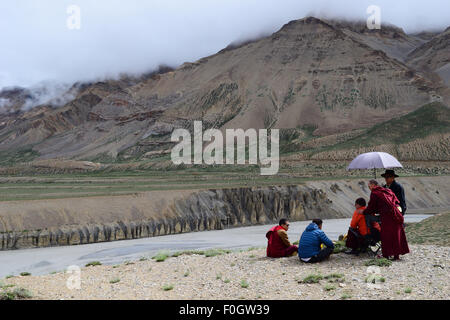 Buddhist Monks relaxing in Himalayas Mountains near frozen himalaya river in Leh Ladakh India - Stock Photo