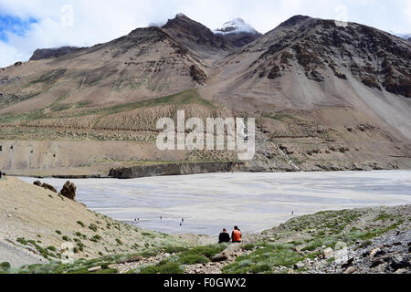 Foreign Tourist Couple Enjoying the Himalayas Mountain and River Beauty in Ladakh India - Stock Photo