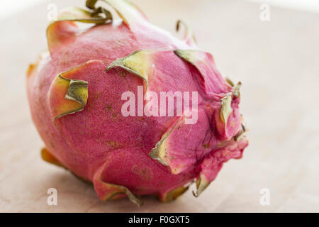 A dragon fruit or pitaya on a wooden surface photographed with window light.