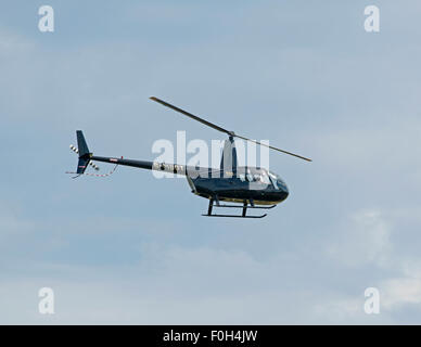 Robinson R44 Raven helicopter (G-MDDT) leaving Inverness Airfield Scotland SCO 10,018. - Stock Photo