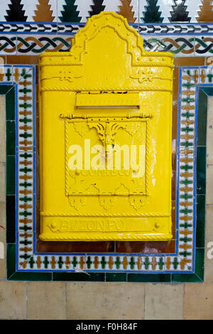 An old wall mounted yellow Post Box on an ornately tiled wall, inside the Spanish railway station of Toledo. - Stock Photo