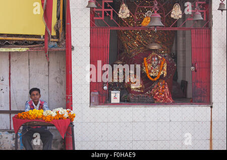 Flower seller at a Hindu shrine in Varanasi, India, for devotees to offer as floral tributes to their God - Stock Photo