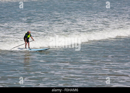A senior paddle boarder rides a wave breaking on the Devon coast. Standup paddle boarding is becoming increasingly - Stock Photo