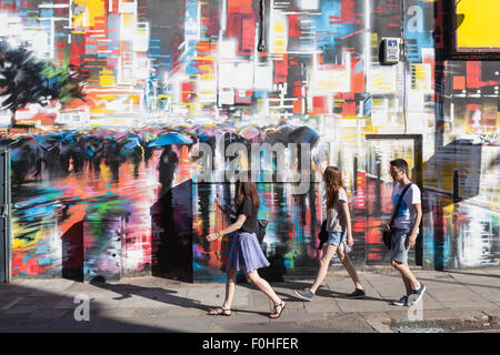 Young people walk past a colourfully painted wall in Camden Town, London. - Stock Photo