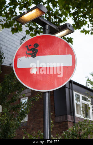 Clet Abraham puts stickers on street signs to alter their meaning. - Stock Photo