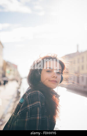 Half length of young beautiful reddish brown hair caucasian woman listening to the music seated on the sidewalk - Stock Photo
