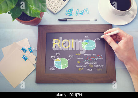 Man drawing ROI concept on chalkboard (return on investment) - Stock Photo