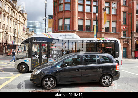 free shuttle bus and car in traffic on deansgate Manchester city centre England UK - Stock Photo