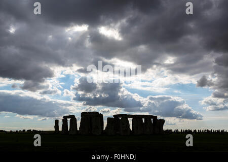 Line of visitors silhouetted next to the stones, Stonehenge, near Amesbury, Wiltshire, England, UK - Stock Photo