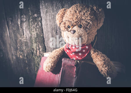 Children teddy bear with old vintage book - Stock Photo