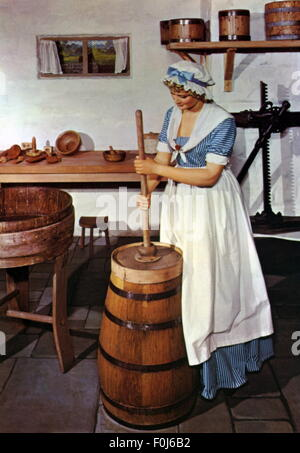household, kitchen and kitchenware, woman at butter churn, re-enacted in a museum, picture postcard, 1950s, Additional - Stock Photo